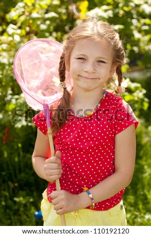 Smiling girl with a pink butterfly net for catching butterflies