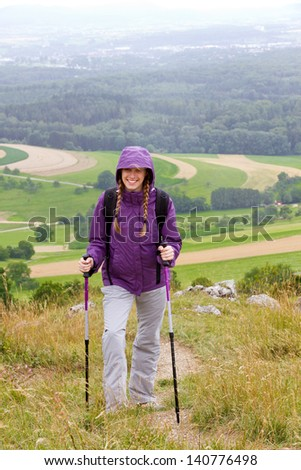 Smiling girl with anorak and hiking sticks walking in rain