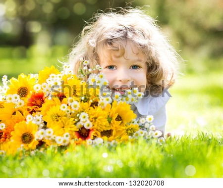 Smiling girl with big bouquet of spring flowers lying on green grass. Mothers day concept