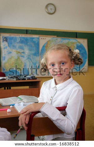 Smiling girl with blue eyes at a geography lesson.