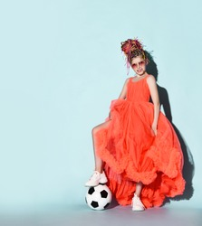 Smiling girl with colorful dreadlocks hairstyle in bright coral dress with fluffy hem, sneakers and suglasses standing with soccer ball under foot over grey background. Girls in football concept