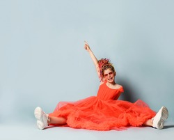 Smiling girl with colorful dreadlocks hairstyle in coral dress with fluffy hem, sneakers and suglasses sitting on floor with legs stretched and feeling excited with raised hand over grey background