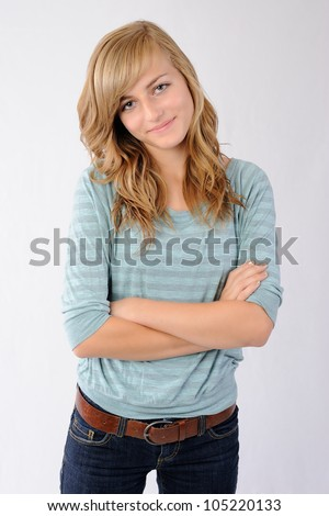 Smiling Girl with Crossed Arms. Thirteen year old girl standing with her arms crossed. Looking at the viewer while smiling. Note: Not Isolated.