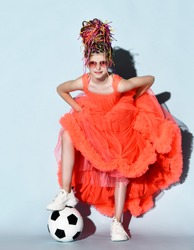 Smiling girl with dreadlocks hairstyle in bright coral big dress with fluffy hem, sneakers and sunglasses standing with soccer ball under foot over grey background. Girls in football concept