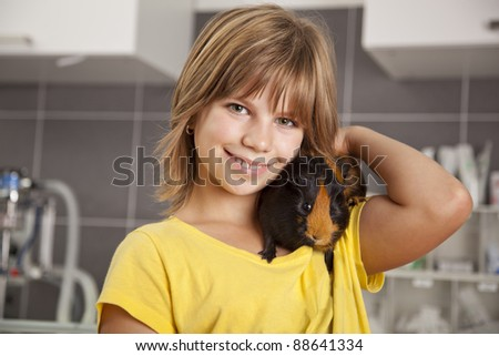 smiling girl with guinea pig on her shoulder standing in a veterinarian practice