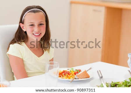 Smiling girl with her dinner at the table