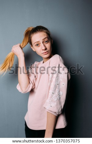 smiling girl with her hair in a ponytail. street style clothing:spring color t-shirt.  emotional portrait of a student with skin problems. model test actress. woman touches a strong and healthy hair #1370357075
