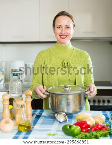 smiling girl with ladle cooking soup in domestic kitchen