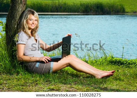 smiling girl with laptop, beautiful blonde woman sitting under a tree near the calm lake
