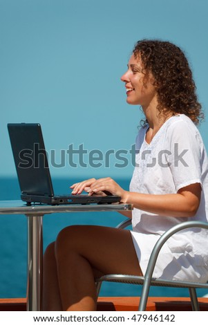 Smiling girl with laptop. Sits at table on beach, warm sunny day. Vertical format.