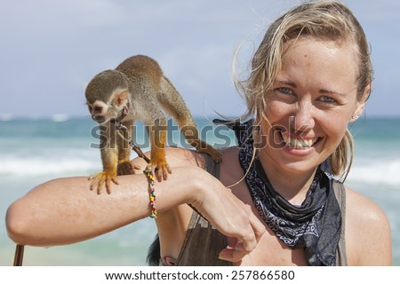 smiling girl with monkey on shoulders