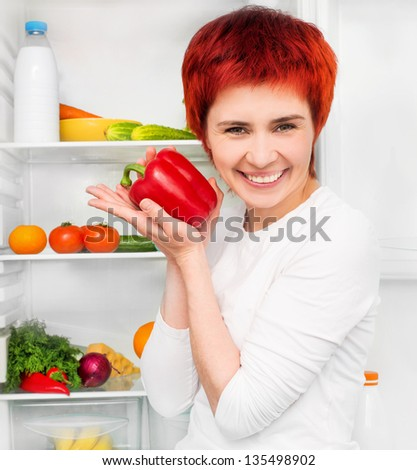 smiling girl with papper against the refrigerator with food