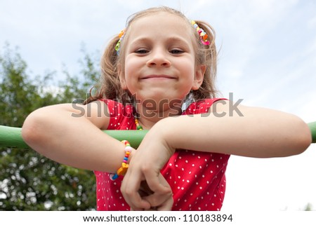 Smiling girl with pigtails plays on the playground