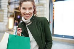 Smiling girl with shopping bags in city