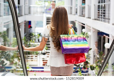 Smiling girl with shopping bags in mall
