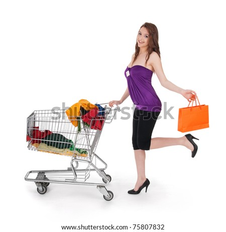 Smiling girl with shopping cart and orange gift bag, isolated on white.