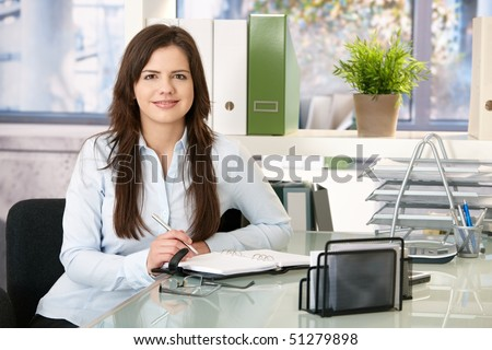 Smiling girl working in office sitting at desk with organizer, looking at camera.