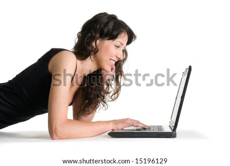 Smiling girl works with the laptop lying on the floor