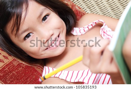 Smiling girl writing with pencil