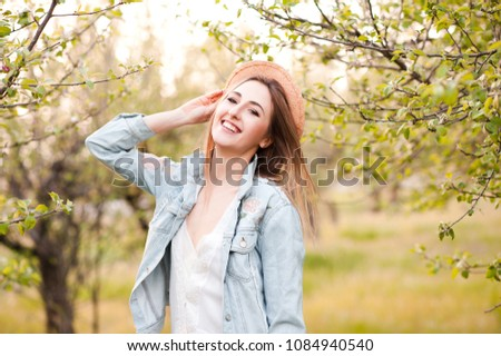 Smiling girl 20-24 year old wearing hat and denim jacket outdoors. Looking at camera. 20s.  Photo stock ©