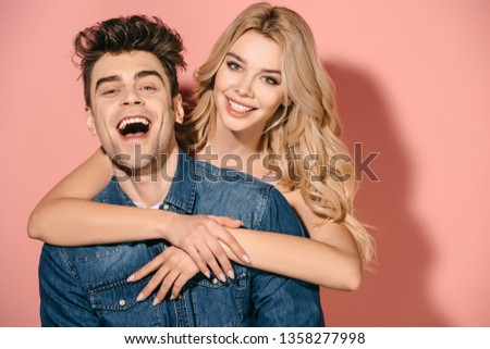 smiling girlfriend and handsome boyfriend in denim shirt hugging and looking at camera   #1358277998