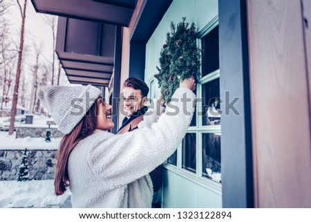 Smiling girlfriend. Smiling girlfriend wearing warm coat and hat putting Christmas wreath on the front door #1323122894