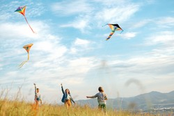 Smiling girls and brother boy with flying colorful kites - popular outdoor toy on the high grass mountain meadow. Happy childhood moments or outdoor time spending concept image.
