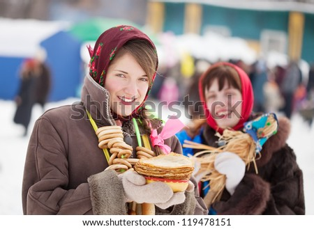 Smiling girls in russian traditional clothes with pancake during  Shrovetide outdoors