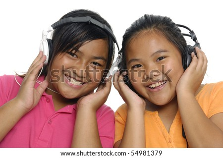 Smiling girls listening to music on headphones isolated over white