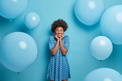 Smiling glad dark skinned woman enjoys birthday party, stands with eyes closed and charming smile, wears fancy blue polka dot summer dress, waits for guests poses around inflated balloons, makes photo