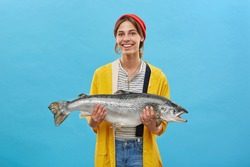 Smiling glad female angler wearing casual clothes returning from night fishing demonstrating her successful catch into camera. Fisherwoman with big salmon in hands isolated over blue background