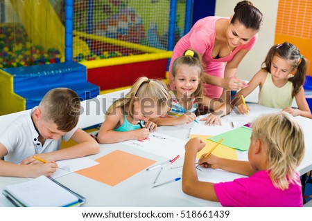 Smiling glad kids drawing together with tutor at hobby group indoors