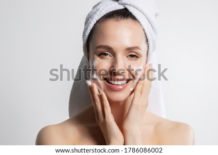 Smiling glad woman applying cosmetic foam portrait. Cheerful laughing millennial washing on face looking at camera. Lovely brunette in head bath towel with attractive appearance. Skincare spa