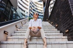 Smiling glamorous attractive positive fashionable blond businesswoman sitting on the stairs in business district.