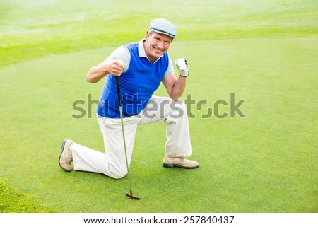 Smiling golfer kneeling on the putting green on a sunny day at the golf course