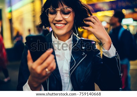 Smiling gorgeous girl in spectacles reading income SMS strolling on night city street in good mood listening music in earphones, female hipster blogging in networks via smartphone enjoying playlist