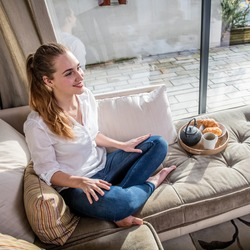 smiling gorgeous young woman with poney tail sitting on a comfortable sofa with her breakfast, tea and croissants in a comfortable home with view on the terrasse