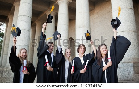 Smiling graduates holding up their hats in front of the university