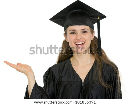 Smiling graduation student girl showing something on empty hand