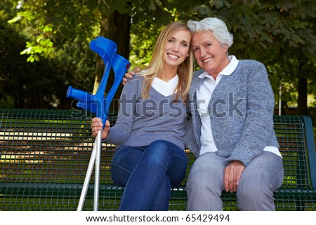 Smiling granddaughter with handicapped grandmother on park bench