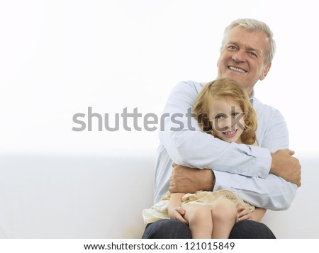 Smiling Grandfather & Granddaughter in his arms. Isolated white background.