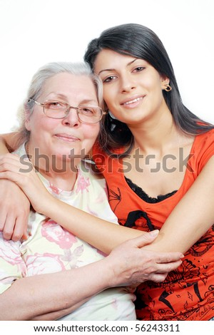 Smiling grandmother and granddaughter embracing,white background ,vertical