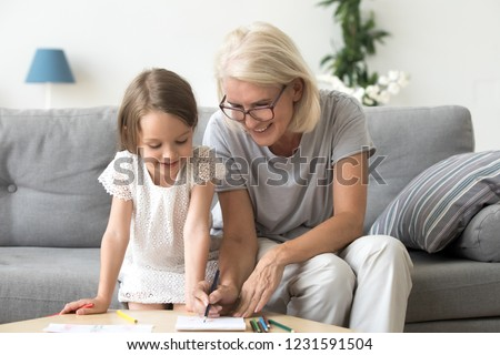 Smiling grandmother and little kid granddaughter drawing on paper with colored pencils together, caring granny teaching grandchild having fun playing at home, grandma and creative child activity