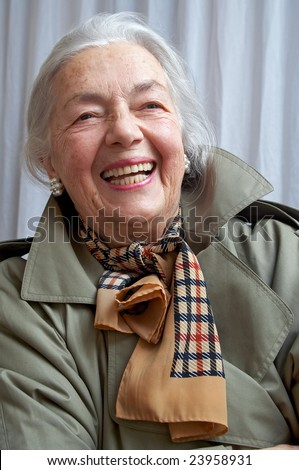 Smiling grandmother in the olive overcoat - stock photo
