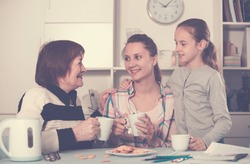 Smiling grandmother, mother and granddaughter drinking tea at home