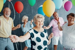 Smiling grandmother wearing a white blouse with black dots and holding colorful balloons during New Year's Eve party with senior friends