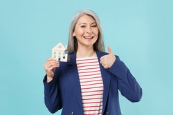 Smiling gray-haired business woman in blue suit posing isolated on pastel blue background. Achievement career wealth business concept. Mock up copy space. Hold house bunch of keys showing thumb up