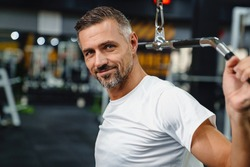 Smiling grey adult sportsman working out with exercise machine in fitness room