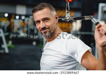 Smiling grey adult sportsman working out with exercise machine in fitness room Foto stock ©