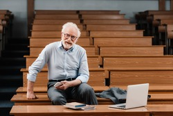 smiling grey hair professor sitting in empty lecture room